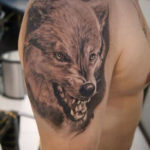 Татуировка оскал волка на плече парня