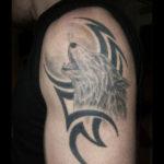 Воющий волк в стиле трайбл на плече парня